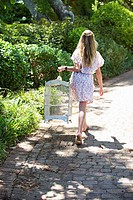 Rear view of a girl walking with a cage in hand