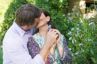 Mature couple kissing in the garden