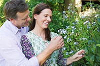 Happy mature couple looking at flowers in a garden