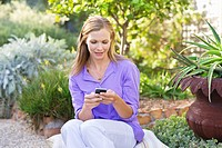 Beautiful young woman text messaging in garden
