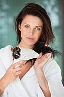 Portrait of a woman drying her hair with a hair dryer