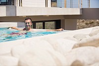 Portrait of a man resting in a swimming pool (thumbnail)
