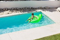 Boy sitting on inflatable ring in swimming pool (thumbnail)