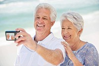 Happy senior couple taking a picture of themselves with a digital camera (thumbnail)