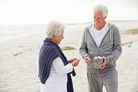Senior couple collecting shell on the beach