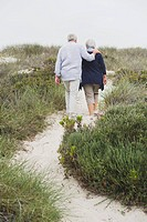 Rear view of a senior couple walking on the beach