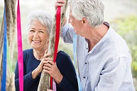 Senior couple standing near a tree decorated with ribbons