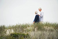 Side profile of a senior couple walking on the beach