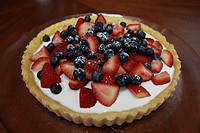 A cream tart containing strawberries and blueberries