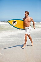 Man running on the beach with surfboard