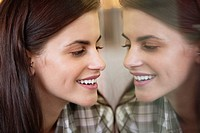 Smiling woman looking at her own reflection in the mirror