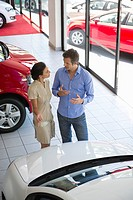 Female salesperson showing car to mid adult man in showroom (thumbnail)