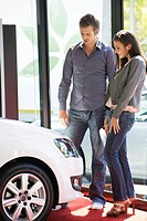 Couple buying a car at showroom