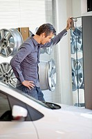Side profile of a mid adult man standing in car showroom