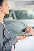 Side profile of a young woman taking car key in showroom