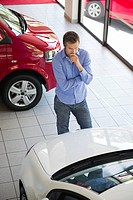 Mid adult man looking at a car in a showroom