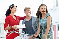 Smiling young man with two women cycling