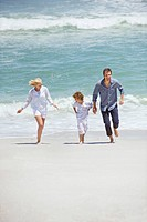 Couple with their son running on the beach