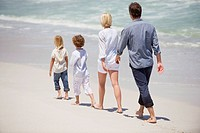Couple with two children walking on the beach
