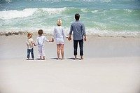 Couple with two children standing on the beach