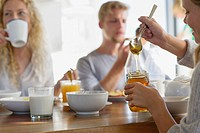 Family eating breakfast at home with focus on a girl taking out honey