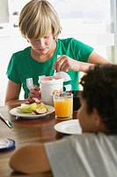Teenage boy having breakfast with his brother sitting in front of him