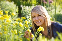 A young lady outdoors in a flower garden
