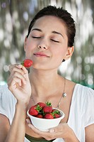 Beautiful young woman holding a bowl of strawberries with her eyes closed