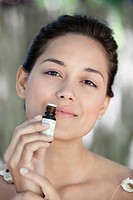 Portrait of a beautiful young woman smelling aromatherapy oil