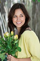 Young woman holding bunch of yellow flowers and smiling