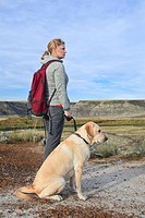 Woman hiking with her male yellow Labrador retriever in the Badlands, Drumheller, Alberta, Canada
