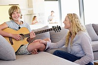 Teenage boy playing a guitar with his mother sitting near him and smiling