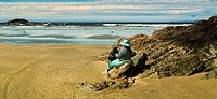 Woman sitting on beach overlooking ocean, Vancouver Island, B.C., Canada