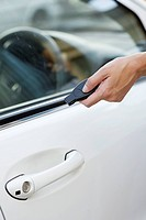 Person's hand unlocking the car with remote control (thumbnail)