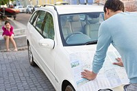 Rear view of a man looking at map on car with young woman sitting in the background