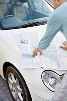 Rear view of a man looking at a map on a car