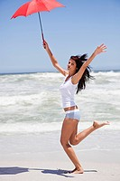 Woman running on the beach with an umbrella (thumbnail)