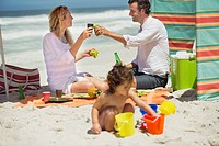Couple toasting with drink while their daughter playing on the beach