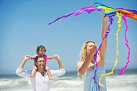 Little girl sitting on father´s shoulder while mother flying shaped kite on the beach