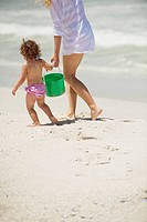 Low section view of a woman walking with her daughter on the beach