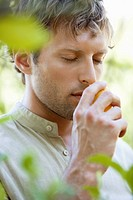 Close_up of a man smelling a lemon