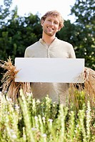 Young man in scarecrow dressing and holding a blank placard in a field