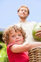Low angle view of father and son holding fruits (thumbnail)