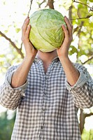 Man holding a cabbage in front of his face