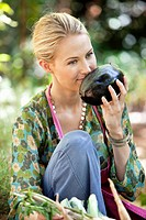 Smiling woman smelling eggplant