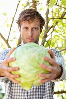 Portrait of a man holding a cabbage
