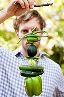 Man holding vegetables hanging on a twig