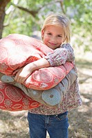 Portrait of a smiling little girl carrying pillows outdoors