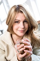 Portrait of a young woman holding a cup of herbal tea
