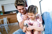 Close_up of a father and his daughter looking at a mobile phone